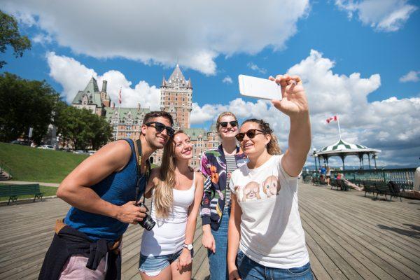 groupe d'amis sur la terrasse dufferin prenant un selfie a l'aide d'un telephone intelligent chateau frontenac en arriere-plan - ete
