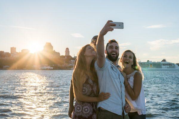 groupe d'amis prenant un selfie apres etre debarque du traversier vue sur le vieux-quebec petit champlain et le chateau frontenac - ete